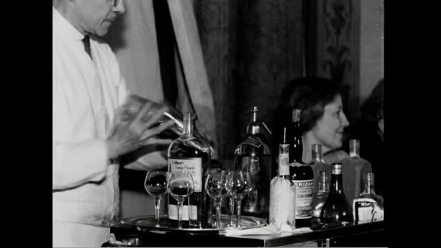 stockvideo's en b-roll-footage met ha view of times square / people drinking and celebrating in night club singing 'hail hail the gang's all here' / bartender making drinks tableside... - 1933