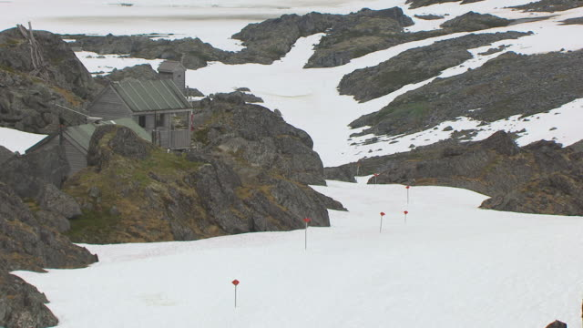 WS AERIAL TU View of top of range and old cabin on Canadian border marking Chilkoot trail summit and hikers on trail / Alaska, United States