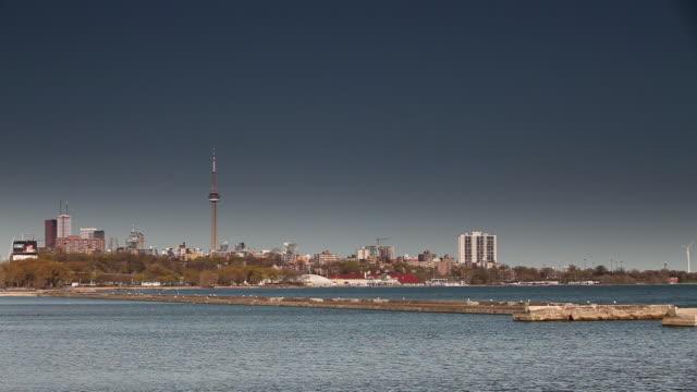 vídeos de stock e filmes b-roll de ws view of toronto skyline with cn tower and windmill in front of lake / toronto, ontario, canada - menos de 10 segundos