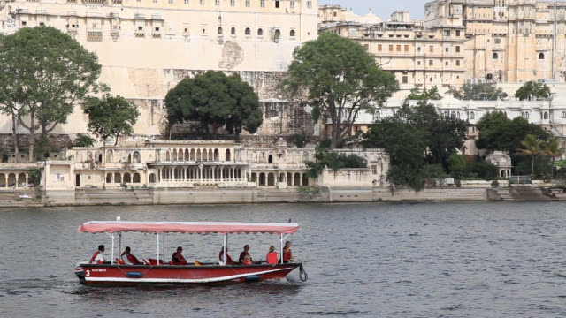 view of tourboat with the tourists passing through lake pichola (an artificial fresh water lake, created in the year 1362 ad) - tourboat stock videos & royalty-free footage
