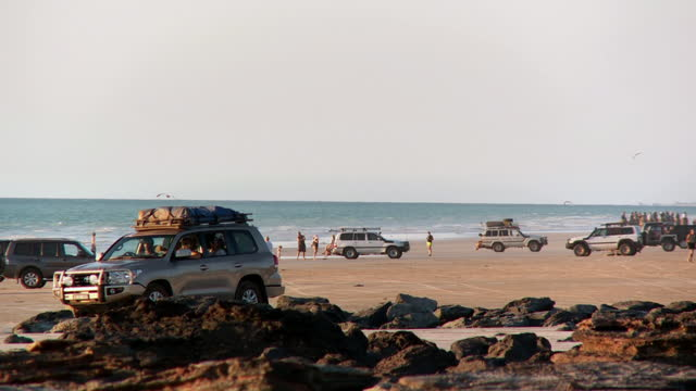 vídeos de stock e filmes b-roll de ws pan view of tourist at broomes cable beach / broome, western australia, australia - cable