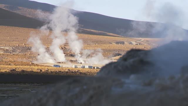vídeos de stock e filmes b-roll de ws view of tourist vehicles among steaming vents at el tatio geysers / san pedro de atacama, norte grande, chile - 50 segundos ou mais
