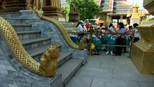 view of tourists and schoolchildren behind temple steps with a naga claw. historically, the serpentine creature supposedly aided buddha. - claw stock videos & royalty-free footage