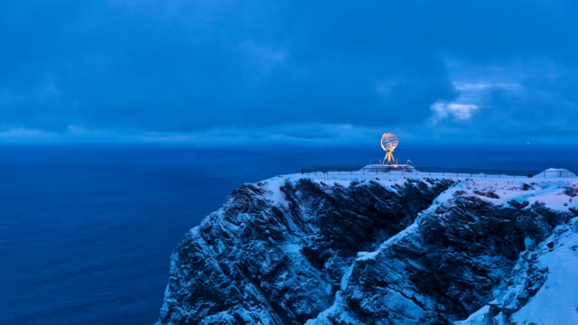 WS T/L View of Tourists and sculpture of globe at North Cape peak / Nordkapp, Mageroya island, South Korea
