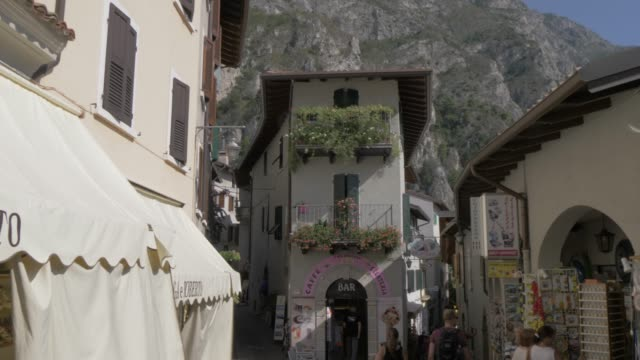 View of tourists and shops in narrow street leading down to lake in Limone sul Garda, Lake Garda, Lombardia, Italy, Europe