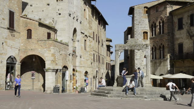 ws view of tourists at well cisterna at piazza della cisterna in medieval village / san gimignano, tuscany, italy - besichtigung stock-videos und b-roll-filmmaterial