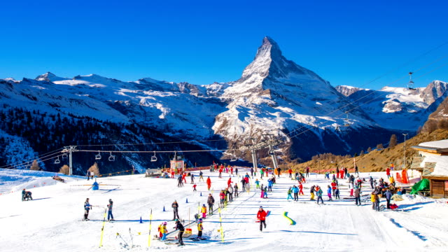 view of tourists enjoying a skiing at matterhorn (a mountain of the alps) - seggiovia video stock e b–roll