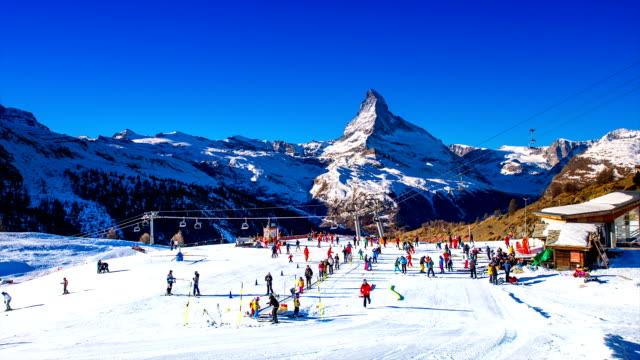 view of tourists enjoying matterhorn (a mountain of the alps) in zermatt - wintersport stock-videos und b-roll-filmmaterial