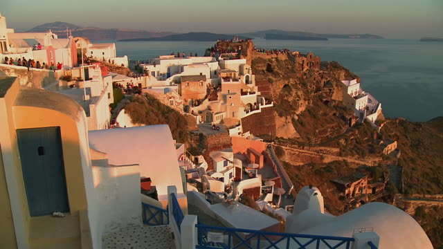 stockvideo's en b-roll-footage met ws view of tourists on hill at sun settin in village oia / santorini, cyclades, greece - oia santorini