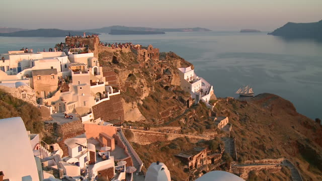 ws view of tourists on hill at sun settin in village oia / santorini, cyclades, greece - oia santorini stock videos & royalty-free footage