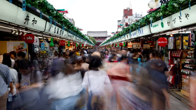 view of tourists on the nakamise-dori shopping street at daytime in asakusa, tokyo, japan - tradition stock videos & royalty-free footage