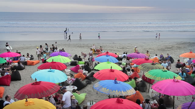 ws view of tourists relaxing beneath umbrellas on beanbags on beach at dusk / seminyak, bali, indonesia - indonesia beach stock videos & royalty-free footage