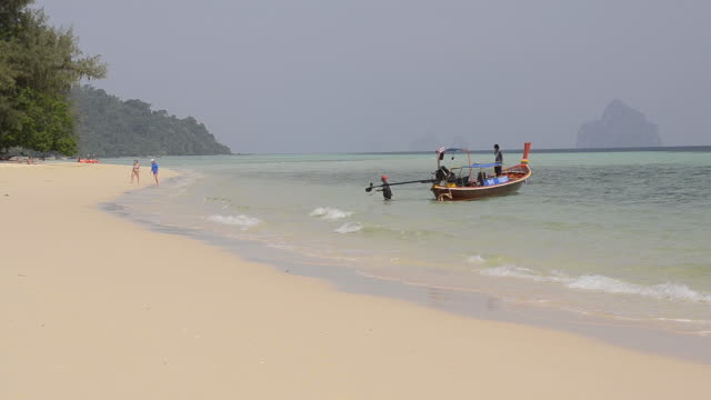 ws view of tourists walking and long tail boat at sandy beach, hat chao mai marine national park / ko kradan, trang, thailand - longtail boat stock videos & royalty-free footage