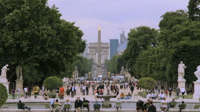 vidéos et rushes de ws view of tourists walking in jardin des tuileries and arc de triomphe in background  /  paris city, paris, france - arc élément architectural
