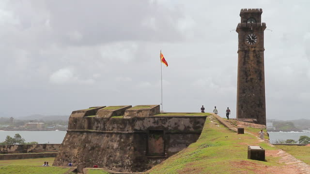 ws view of tourists wander around historic clock tower and rampart walls of galle fort / galle, southern province, sri lanka - clock tower stock videos & royalty-free footage