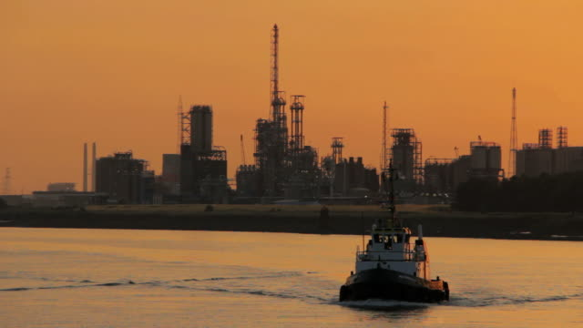 WS View of tow boat moving against petroleum industry at dusk  / Antwerp, Antwerp, Belgium