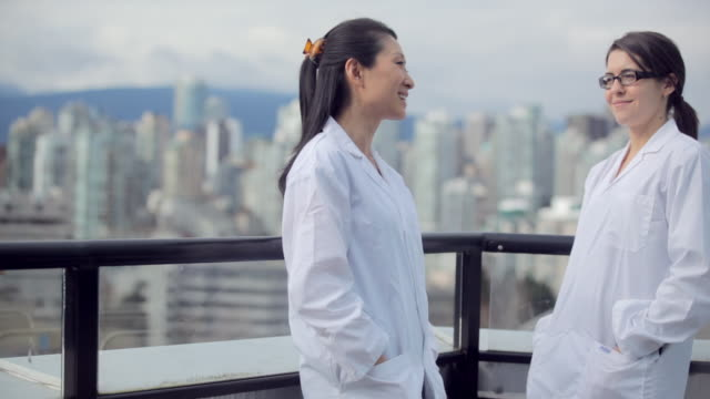ms pan view of tow female medical professionals discussion each other / vancouver, bc, canada - other stock videos & royalty-free footage