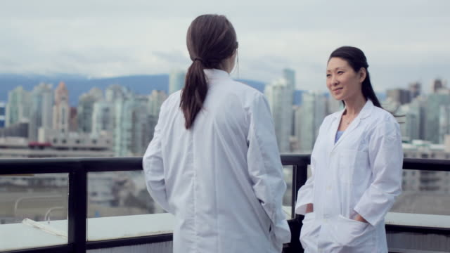 MS PAN View of tow female medical professionals discussion each other / Vancouver, BC, Canada