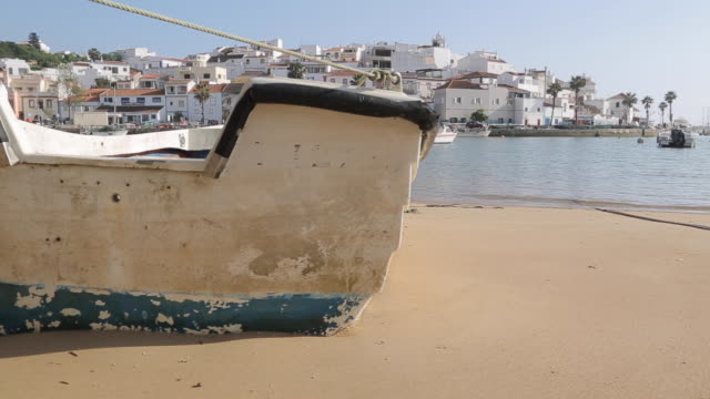 view of town and boats on beach, ferragudo, algarve, portugal, europe - portuguese culture stock videos & royalty-free footage