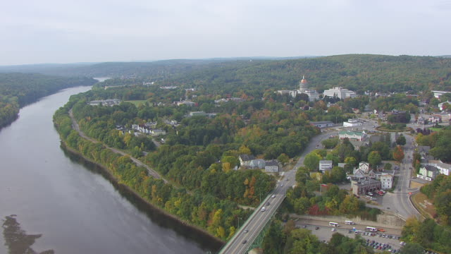 ws aerial pov view of town and bridge, maine state house in background / augusta, maine, united states - augusta maine stock videos & royalty-free footage