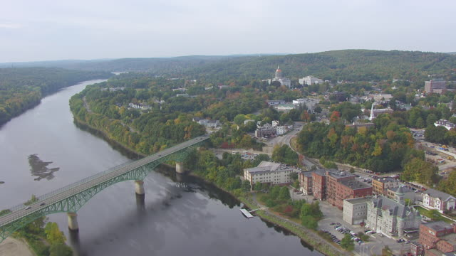 ws aerial pov view of town and bridge, maine state house in background / augusta, maine, united states - maine stock videos & royalty-free footage