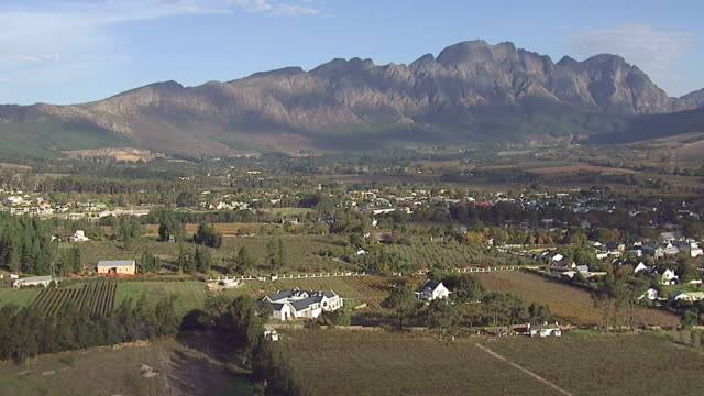 ws aerial view of town and farmland in front of mountains / western cape, south africa - paarl stock videos & royalty-free footage