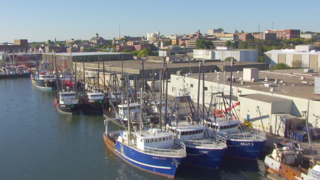 ws aerial pov view of town and waterfront, fishing boat moored near dock / new bedford, massachusetts, united states - new bedford stock videos & royalty-free footage