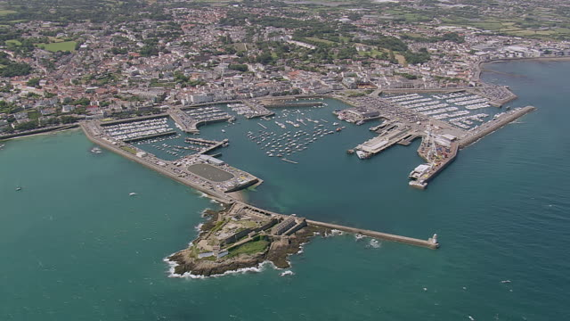 ws aerial view of town besides coastline / guernsey, channel isles - guernsey stock-videos und b-roll-filmmaterial