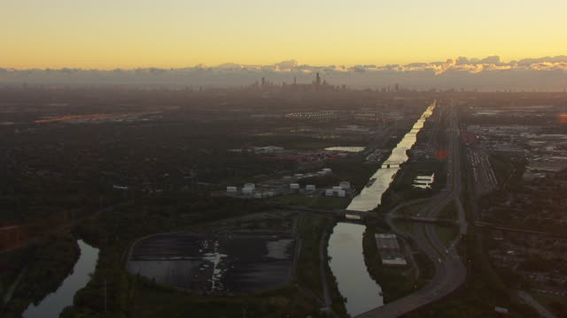 WS AERIAL POV View of town with river and freeway maze, skyline in background / Romeoville, Will County, Illinois, United States