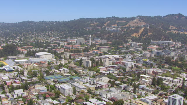 ws aerial pov view of townscape and university of california with sather tower in back of berkeley hills / berkeley, california, united states - university of california stock videos & royalty-free footage