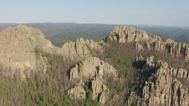 WS AERIAL View of track along tree covered rock formations in Black Hills National Forest in Pennington County and reveal valley / South Dakota, United States