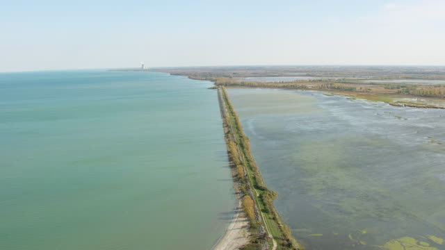 ws aerial view of track barrier between lake erie and wetlands / ohio, united states - lago erie video stock e b–roll