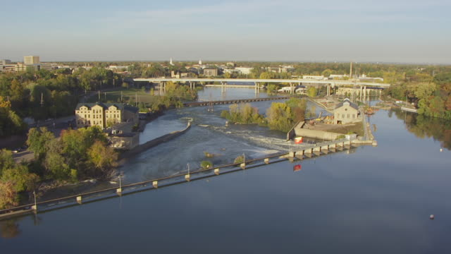WS AERIAL View of track down the Fox River and fly over the Fox River Dam / Appleton, Wisconsin, United States