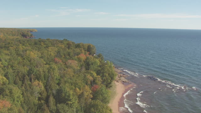 ws aerial view of tracking along coastline of outer island with lake superior / wisconsin, united states  - lago superiore video stock e b–roll