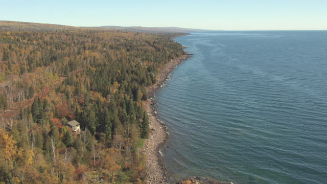 ws aerial view of tracking along rocky shore of lake superior / minnesota, united states - lago superiore video stock e b–roll