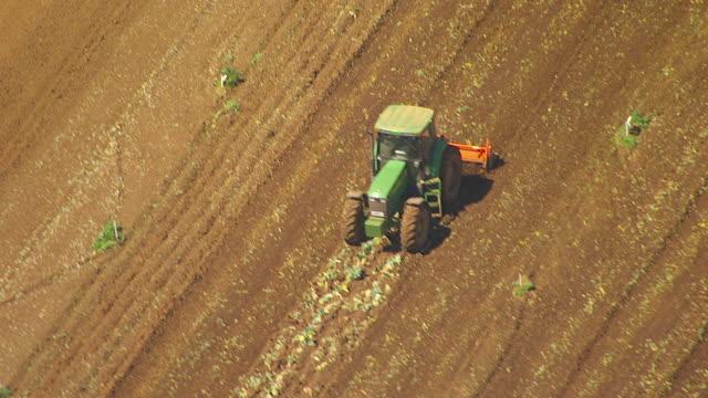vídeos de stock e filmes b-roll de ws aerial zi view of tractor ploughing in field / werribee, victoria, australia - trator