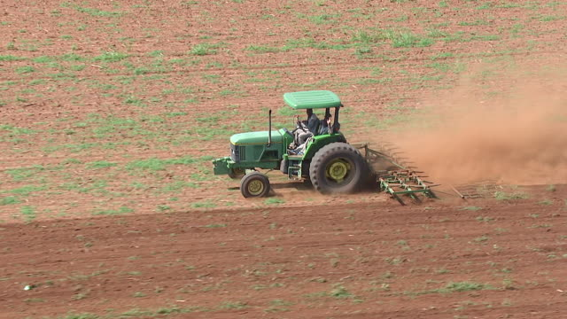 ms aerial ts view of tractor ploughing through field / polokwane, north west province, south africa - pflügen stock-videos und b-roll-filmmaterial