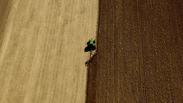 ms aerial view of tractor plowing vertical rows in soil / oregon, united states - pflug stock-videos und b-roll-filmmaterial