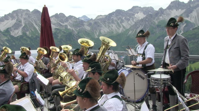 ms view of traditional band at fellhorn / oberstdorf, bavaria, germany  - musikinstrument stock-videos und b-roll-filmmaterial
