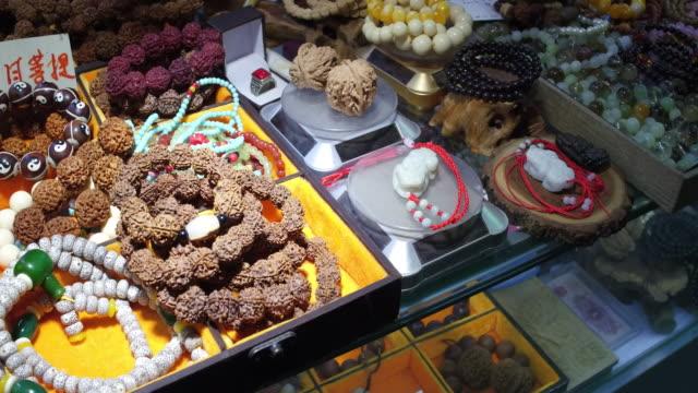 vídeos de stock e filmes b-roll de a view of traditional chinese artifact in famous wangfujing snack street on may 4 2017 in beijing china wangfujing is a main business street for... - gema semipreciosa