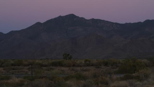 ws view of traffic along highway at dusk with mountains beneath purple sky / kingman, arizona, united states - kingman arizona stock videos & royalty-free footage