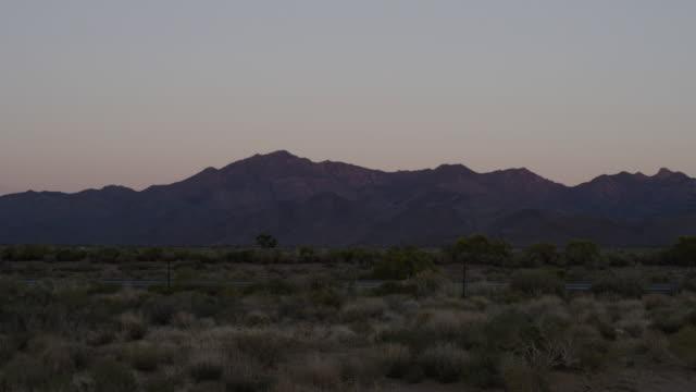 ws view of traffic along highway at dusk with mountains / kingman, arizona, united states - kingman arizona stock videos & royalty-free footage