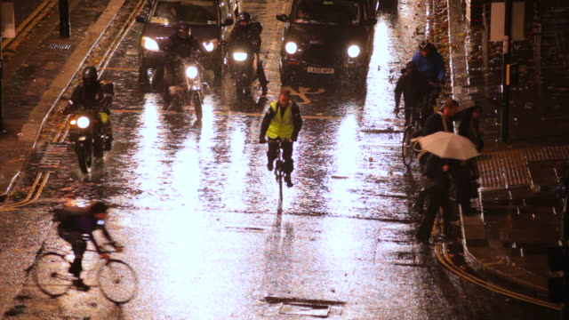 WS View of Traffic and pedestrians on London Wall in evening rushhour rain / London, United Kingdom