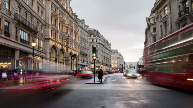 ws t/l view of traffic and pedestrians passing on regent street near oxford circus in wet winters day rush hour / london, greater london, united kingdom - uk video stock e b–roll