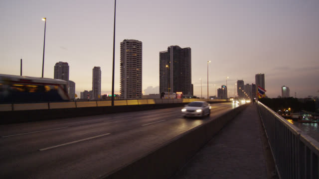 ws view of traffic and sky train on taksin bridge at dusk  / bangkok, thailand - sydostasien bildbanksvideor och videomaterial från bakom kulisserna