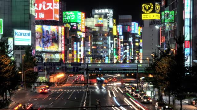 WS T/L View of traffic and trains passing through colorful neon's of Shinjuku at night / Tokyo, Japan