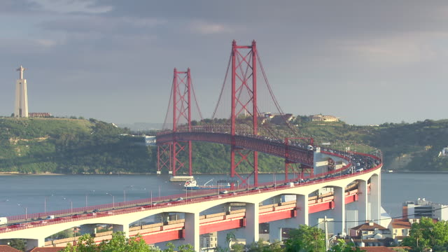 """ws view of traffic at""""ponte 25 de abril"""" while cargo ship is crossing tagus river and """"cristo rei"""" / lisbon, portugal   - bridge built structure stock videos & royalty-free footage"""