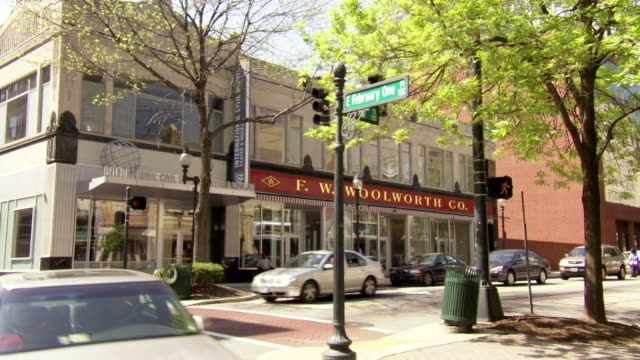 stockvideo's en b-roll-footage met ws pan view of traffic flowing in front of international civil rights center and museum f w woolworth building in downtown city / greensboro, north carolina, united states - straatnaambord