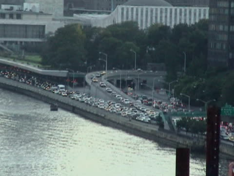view of traffic jam near united nations building as pedestrians in foreground cross queensboro bridge during citywide blackout on august 14 2003 /... - 2003年点の映像素材/bロール