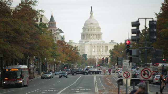 WS View of Traffic moving in front of Dome of US capitol building wide down Pennsylvania avenue / Washington, District of Columbia, United States
